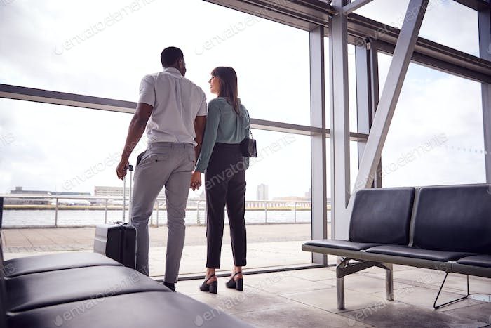 Rear View Of Business Couple With Luggage Standing By Window In Airport Departure Lounge