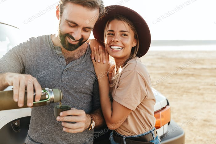 Loving couple outdoors at beach near car.