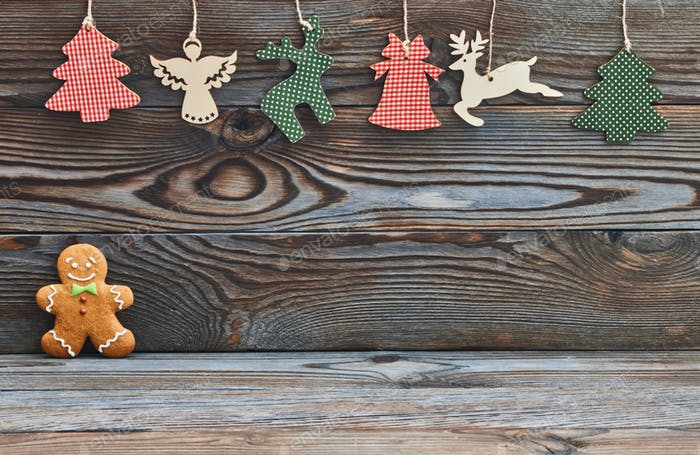 Christmas homemade gingerbread man on wooden background and decoration
