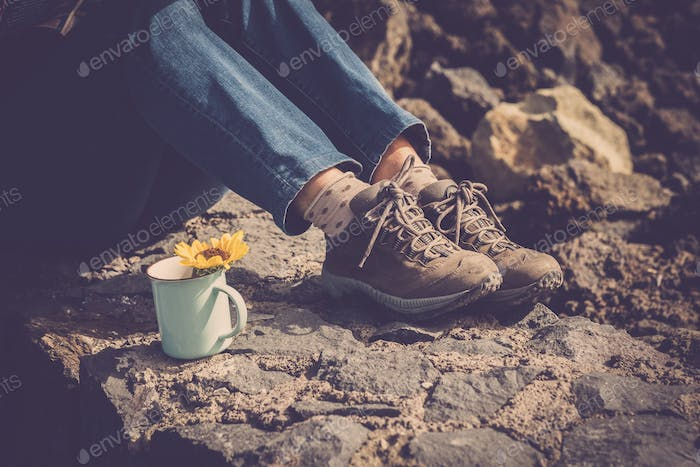 Close up of woman legs and jeans and trekking shoes - rest and relaxed with travel cup