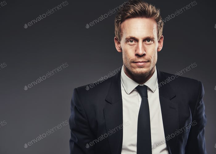 Blond young man wearing business black suit
