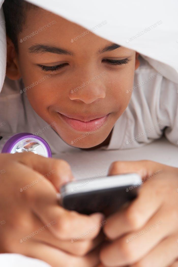 Niño Uso teléfono Móvil debajo del edredón