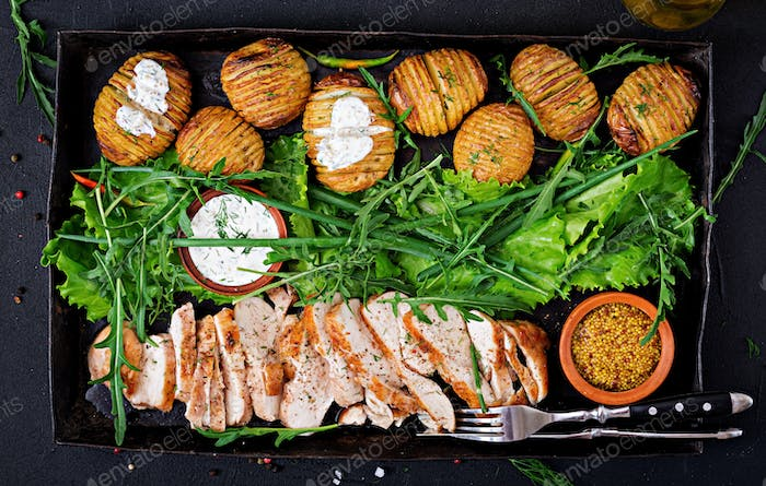 Chicken fillet cooked on a grill with a garnish of baked potatoes.