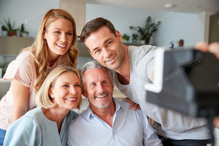 Senior Parents With Adult Offspring Posing For Selfie On Vintage Instant Film Camera