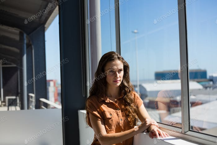 Thoughtful businesswoman looking away while standing by window