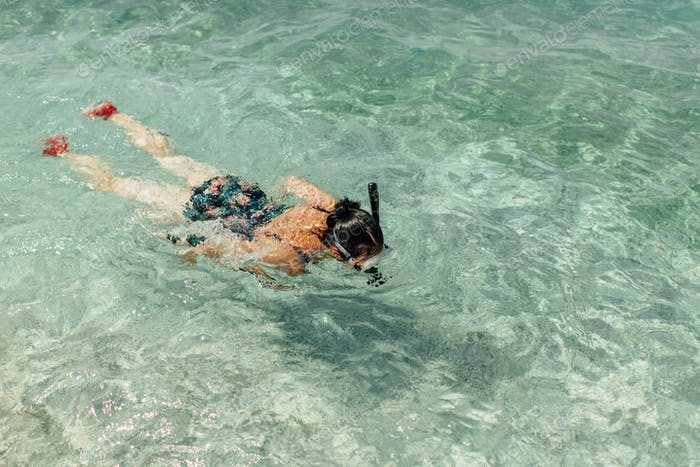 Top view of female swimmer snorkeling in sea.