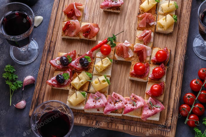 Close view of tiny spanish tapas with jamon, sausage, cheese and wine