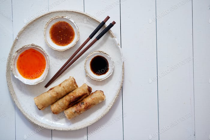 Fried Chinese Thai or Vietnamese traditional spring rolls or nems served on ceramic plate