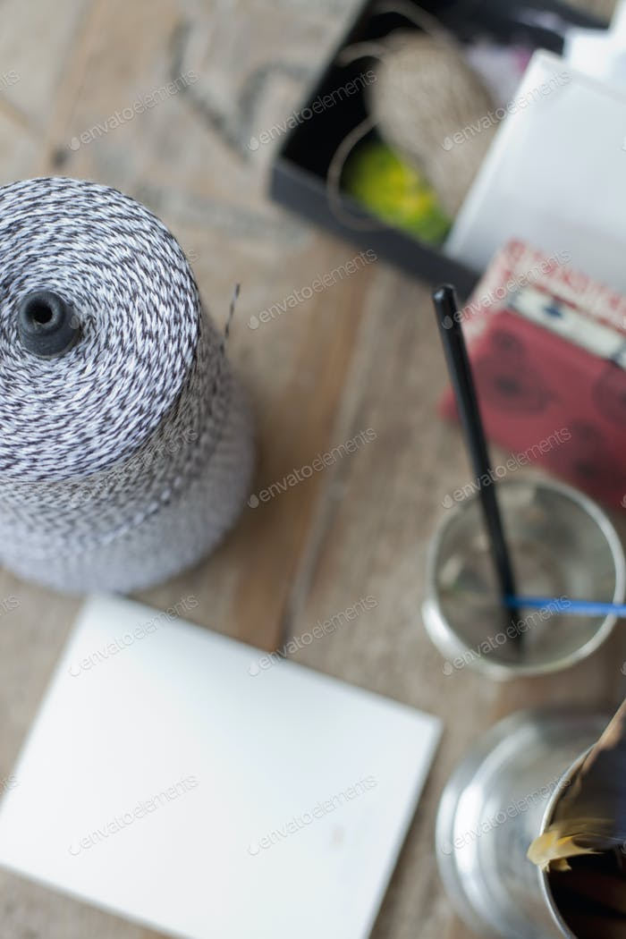 A table top with a small group of objects. Tankard and pencils, paper and a large ball of string.
