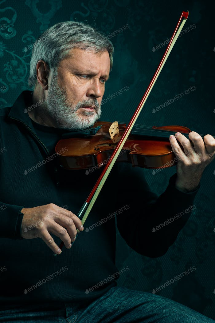 Senior musician playing a violin with wand on black background