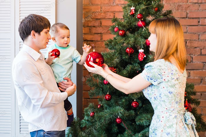 Happy family decorating a Christmas tree with baubles in the living-room