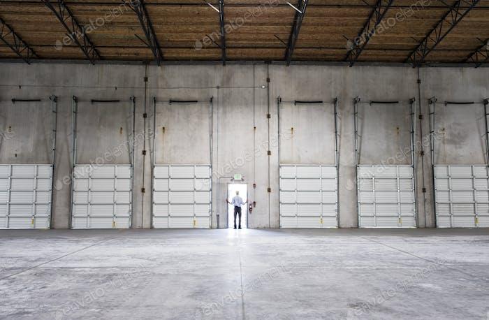 Mann Stehende Tür des neuen Lagers wartet auf die Ankunft des ersten LKW mit Neugeschäft.