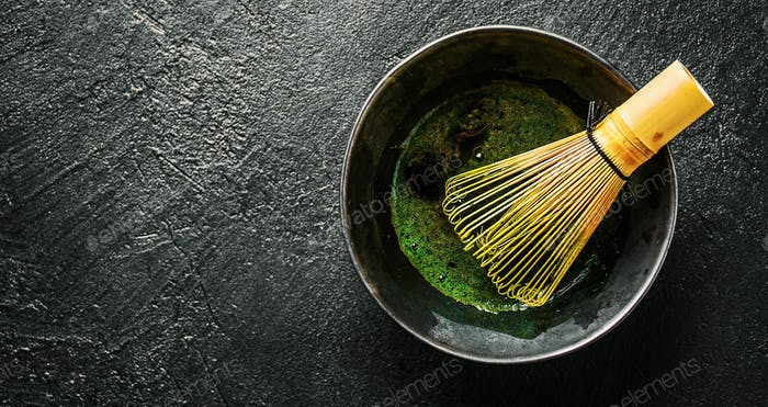 Matcha tea in black bowl on dark