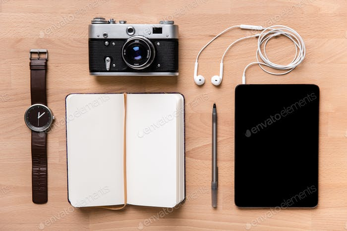 Notebook, blank screen tablet with earphones, camera, watch and pen