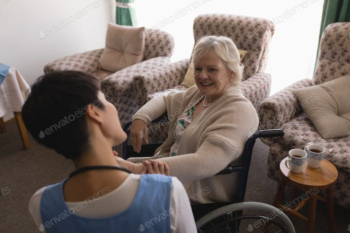 Female doctor interacting with disabled senior woman in living room at home