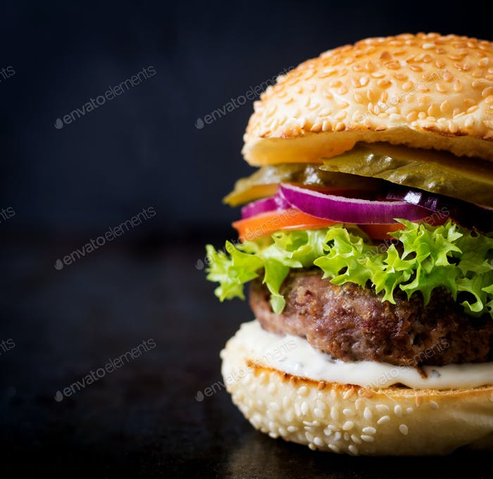 Big sandwich - hamburger burger with beef, pickles, tomato and tartar sauce on black background.