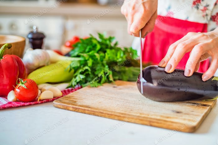 Female hand with knife cuts eggplant in kitchen. Cooking vegetables