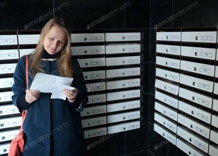 Glückliche Frau, die einen Brief liest