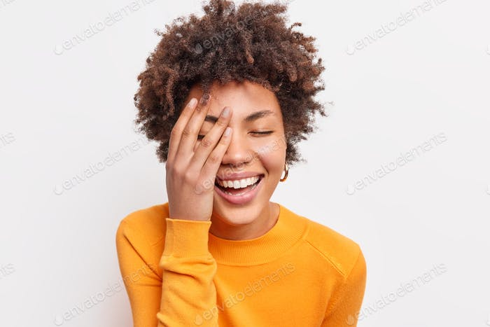 Close up shot of joyful carefree young woman with curly Afro hair smiles toothily keeps eyes closed
