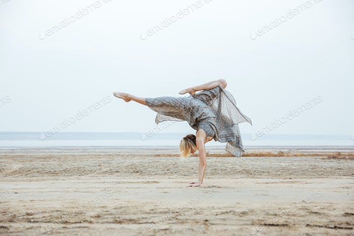 Woman standing on arms and posing at the beach