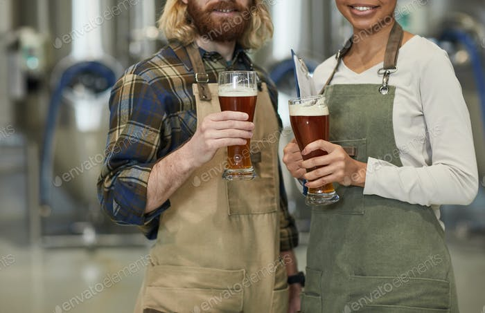 Two Workers Holding Beer Glasses at Brewery