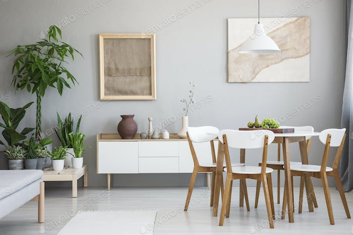 Real photo of bright dining room interior with wooden table and
