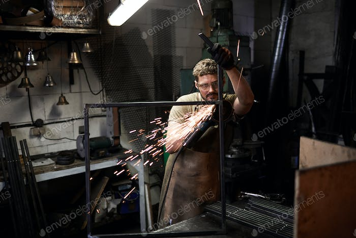 Young worker making metal frame
