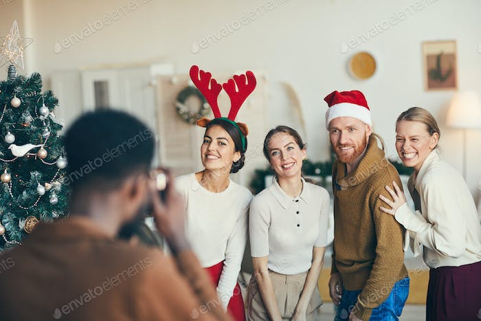 Group of Friends Taking Photos at Christmas Party