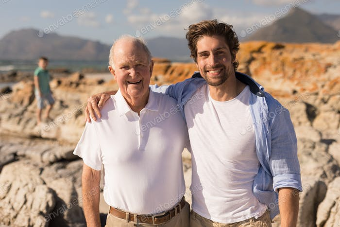 Front view of happy father and son with arms around looking at camera on beach