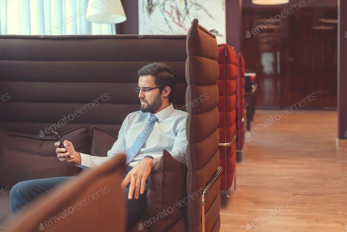 Junger Geschäftsmann mit einem Telefon