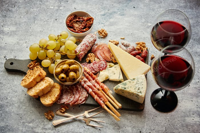 Cold snacks board with meats, grapes, wine, various kinds of cheese