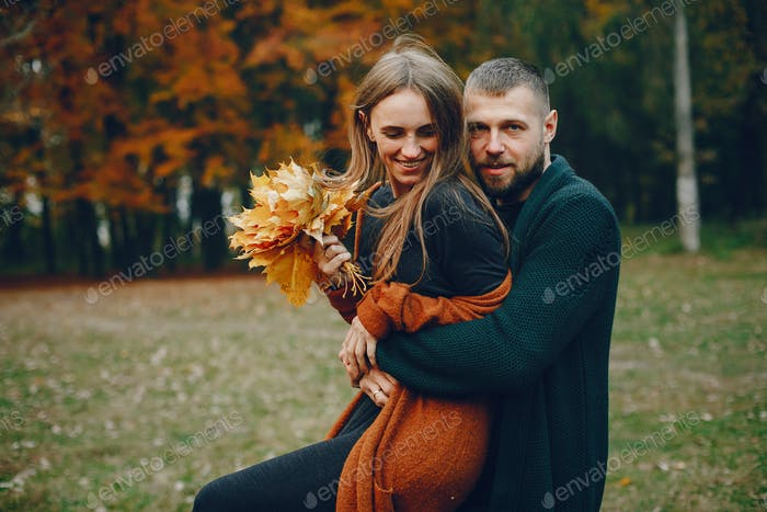 Elegant couple spend time in a autumn park