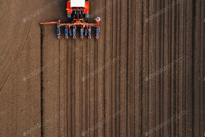 Aerial view of tractor with mounted seeder performing direct see