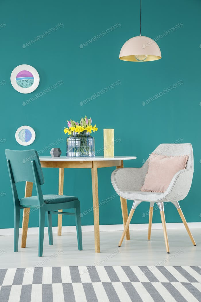 Chair, armchair with a pillow, dining table, striped carpet and
