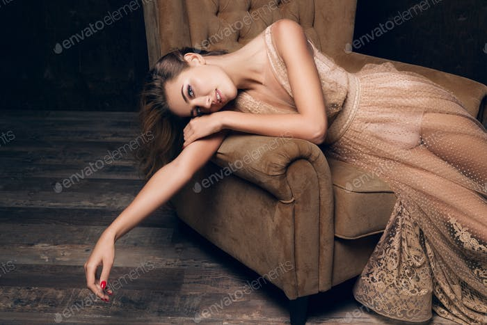 beautiful woman in evening dress sitting in chair, luxury glamour style