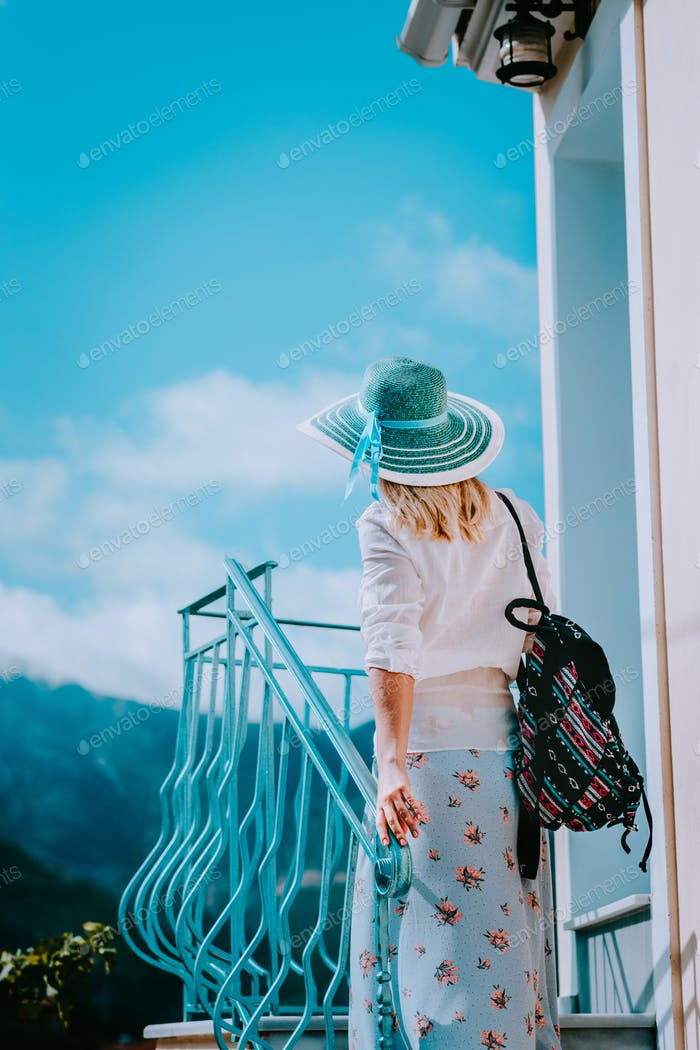 Young woman wearing summer clothes and straw hat going up stairs on sunny day. Vacation holidays in