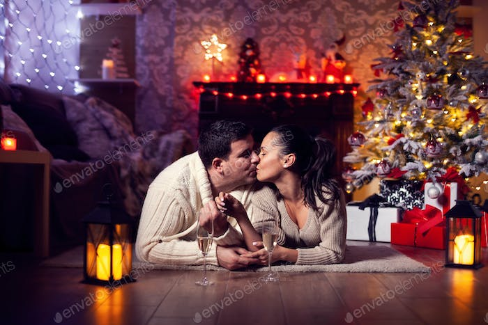 Joyful couple near christmas tree and fireplace in romantic lighting