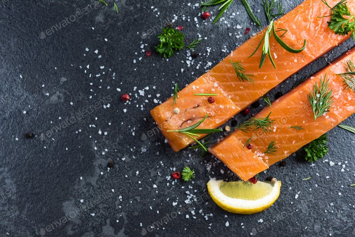 Salmon fish fillets on dark marble table