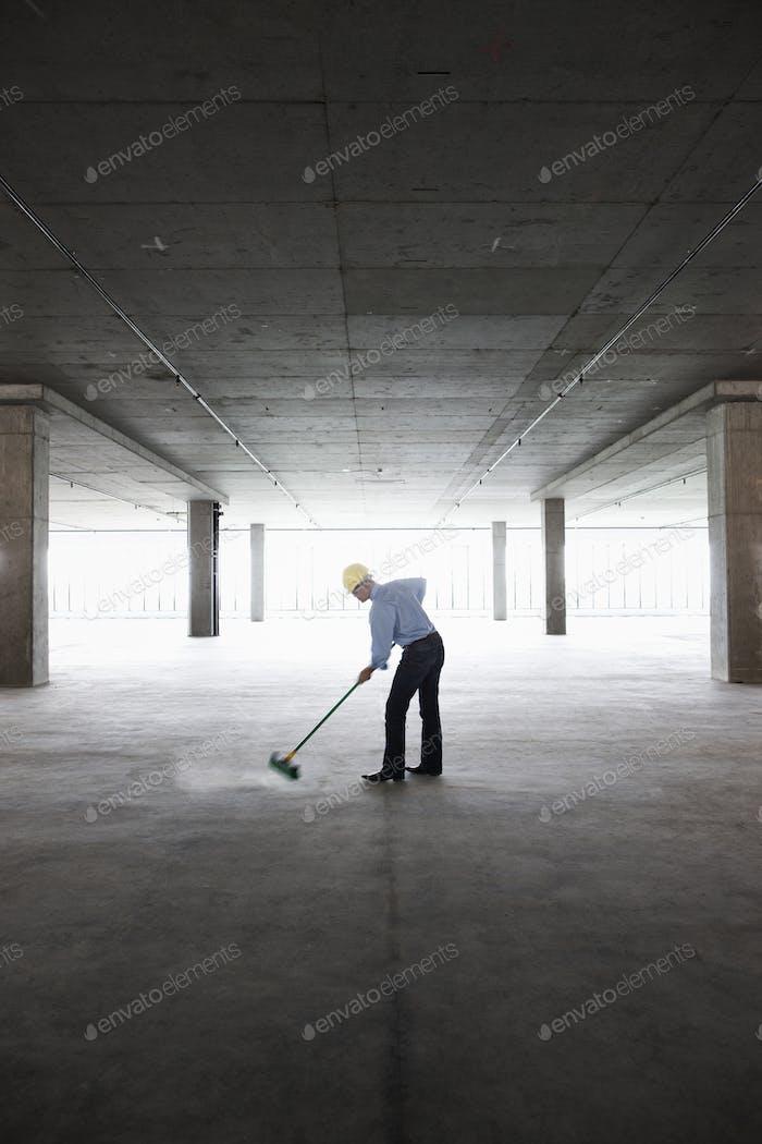 Asiatische Geschäftsmann aufräumen mit einem Besen in einem großen leeren rohen Bürofläche.