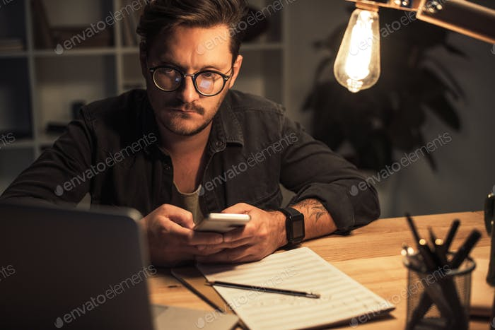 young thoughtful composer using smartphone at workplace in evening
