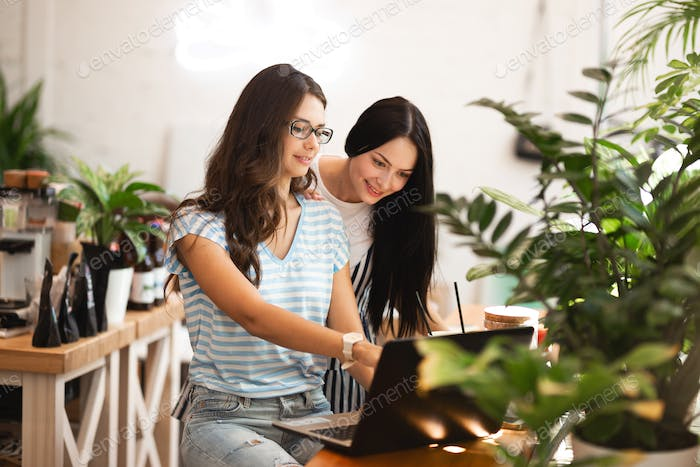 Two cute slim girls with long dark hair,wearing casual style,sit at the table and look attentively