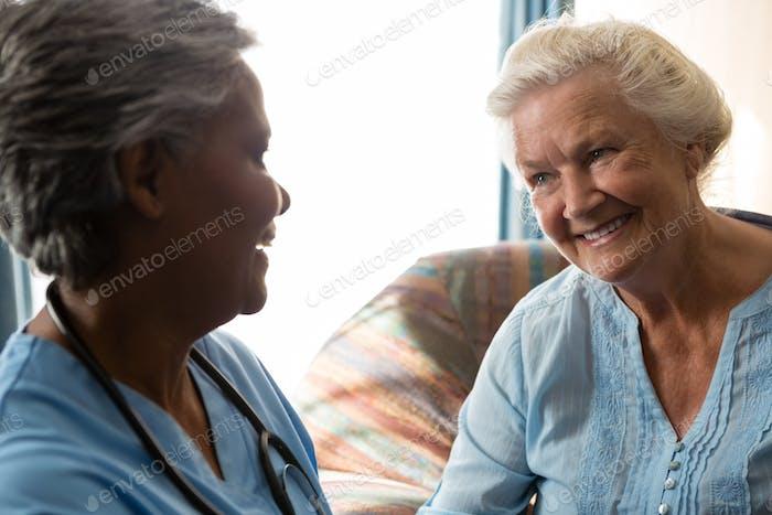 Krankenschwester im Gespräch mit älteren Patienten im Pflegeheim