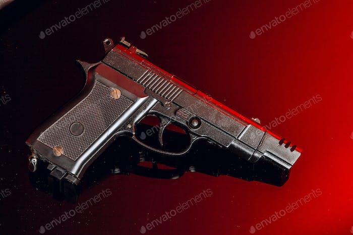 Black handgun on black background with reflection