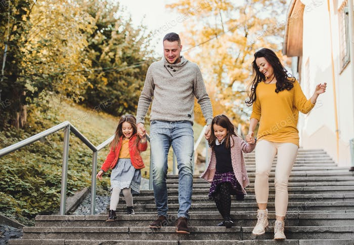 A young family with children walking down the stairs outdoors in town in autumn.
