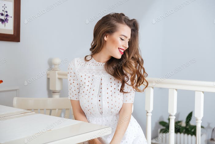 Happy lovely young woman in white dress sitting at cafe