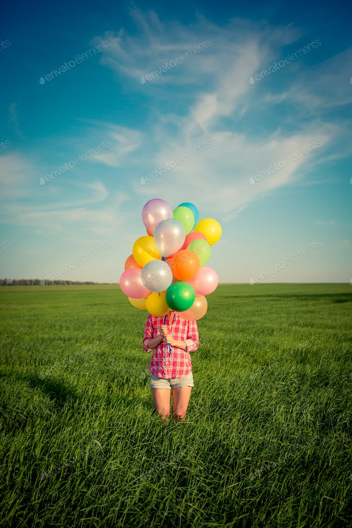 Woman with toy balloons in spring field