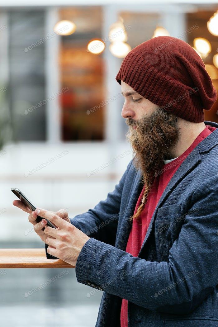 Guapo hipster de moda en sombrero y chaqueta azul usando el teléfono inteligente en interiores