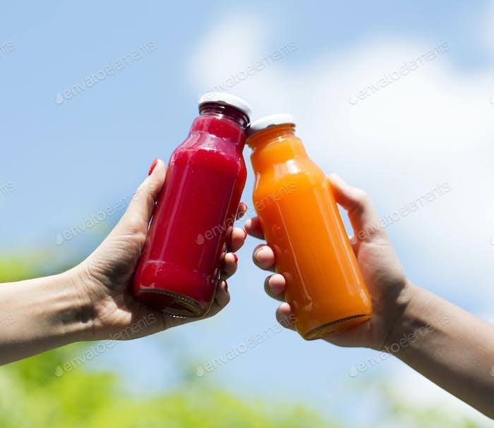 Detox summer cocktails in woman hands outdoor over blue sky