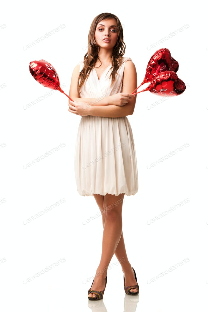 Young beautiful positive brunette woman in beige dress standing, holding red heart shaped balloons