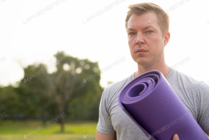 Young handsome man with yoga mat at the park